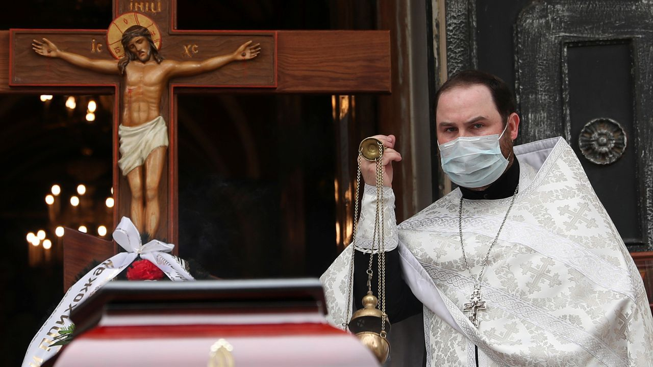 Un sacerdote con una máscara protectora celebra un servicio funerario junto al ataúd del diácono ortodoxo Andrei Molchanov,  quien murió después de contraer la enfermedad por coronavirus en Moscú
