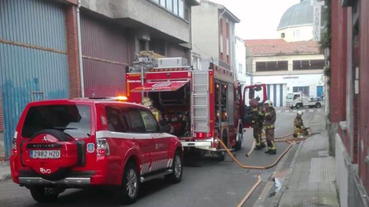 Los bomberos apagan el fuego en una nave en Almacenes Industriales, en Oviedo