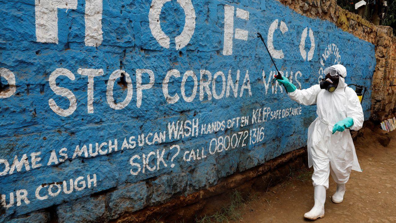 Un trabajador desinfecta un mural contra el coronavirus en Nairobi, Kenia