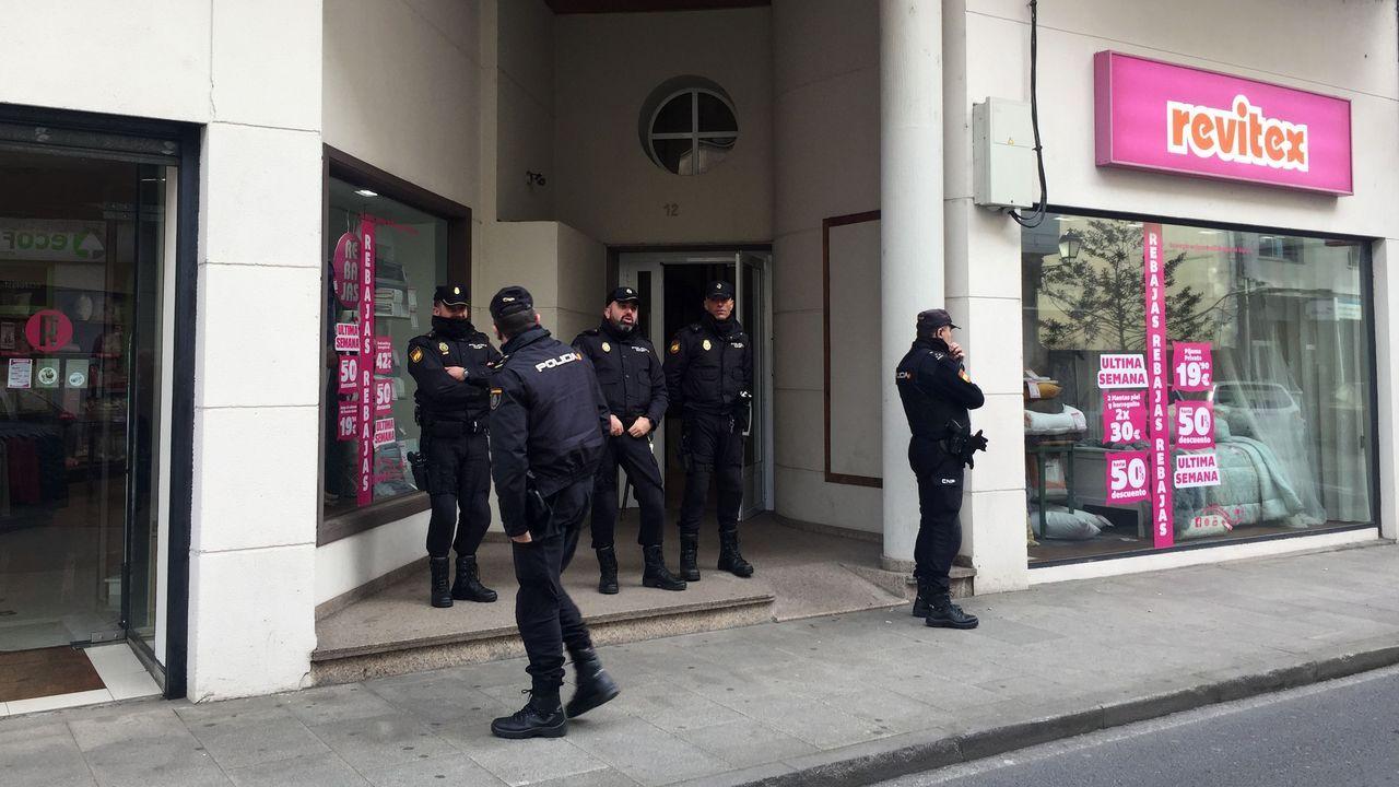 Policías frente al portal del barrio de San Antonio en el que está uno de los pisos registrados en Monforte