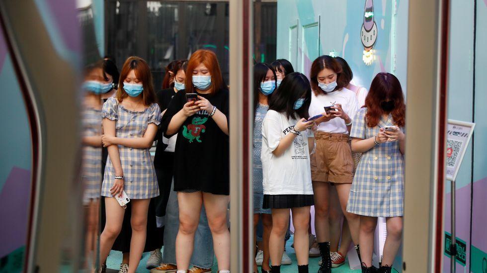 Jóvenes chinas sostienen sus móviles mientras esperanque empiece un evento promocional del servicio de streaming QQ Music, en Pequín