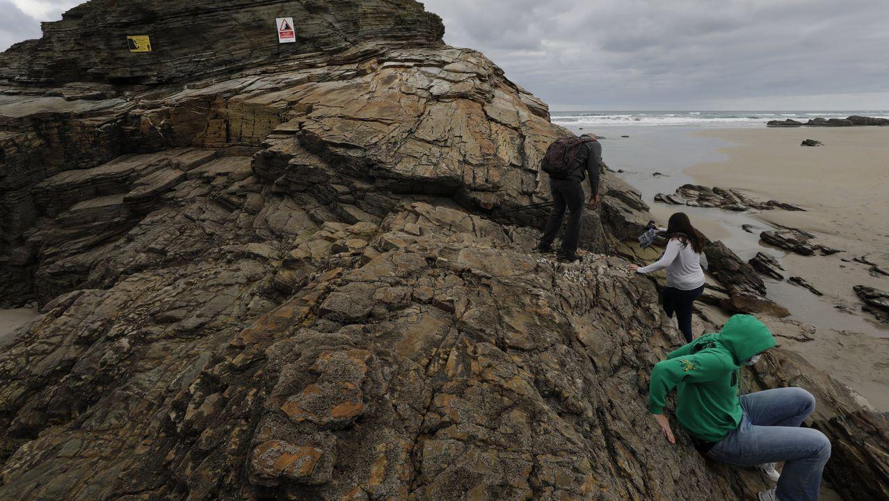 La playa del Matadero se queda sin arena.Pese a los avisos, la gente trepa a las rocas de As Catedrais, algo prohibido