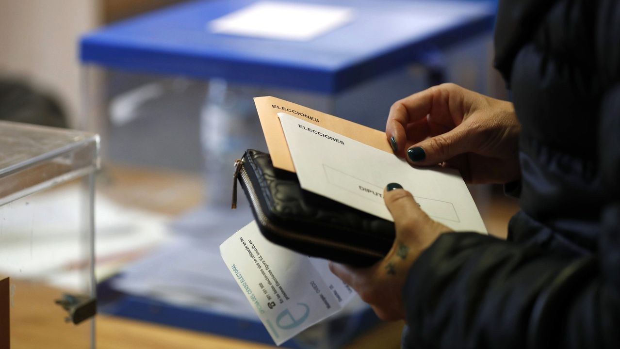 Una mujer con sus papeletas espera para votar en un colegio electoral de Oviedo