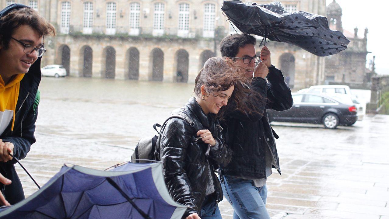 El fuerte viento hace hoy imposible abrir el paraguas en Santiago