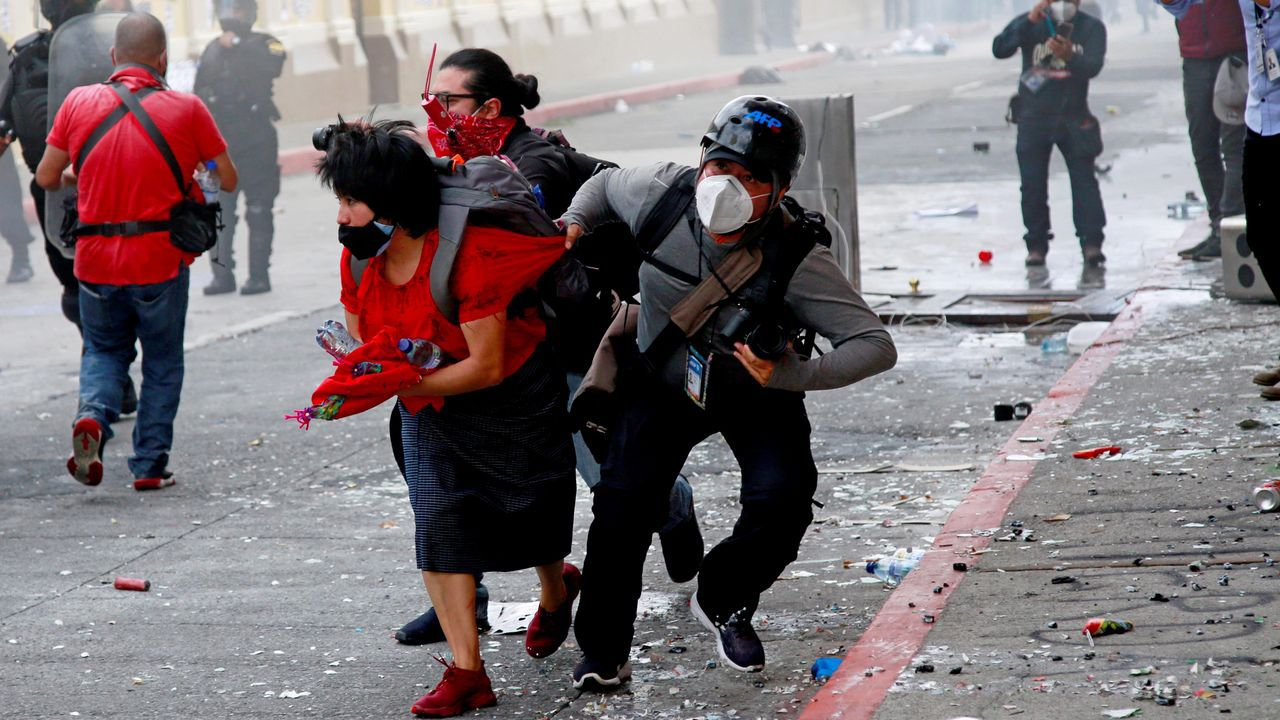 Un fotografo ayuda a una manifestante herida