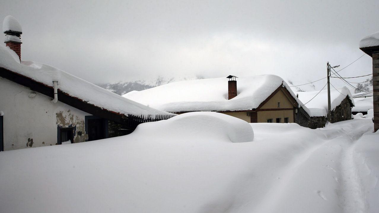 Carretera abierta alrededor de la nieve en Somiedo.Un vehículo cubierto de nieve, en el pueblo asturiano de Pajares