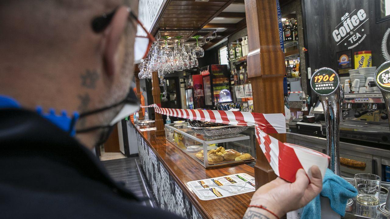 Un hostelero de Noia precinta la barra, en las que no se puede consumir desde ese jueves en Galicia