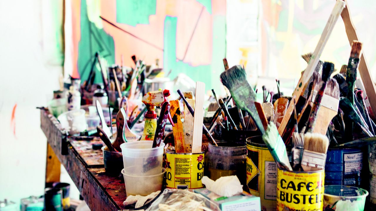 Un montón de pinceles y botes de pintura