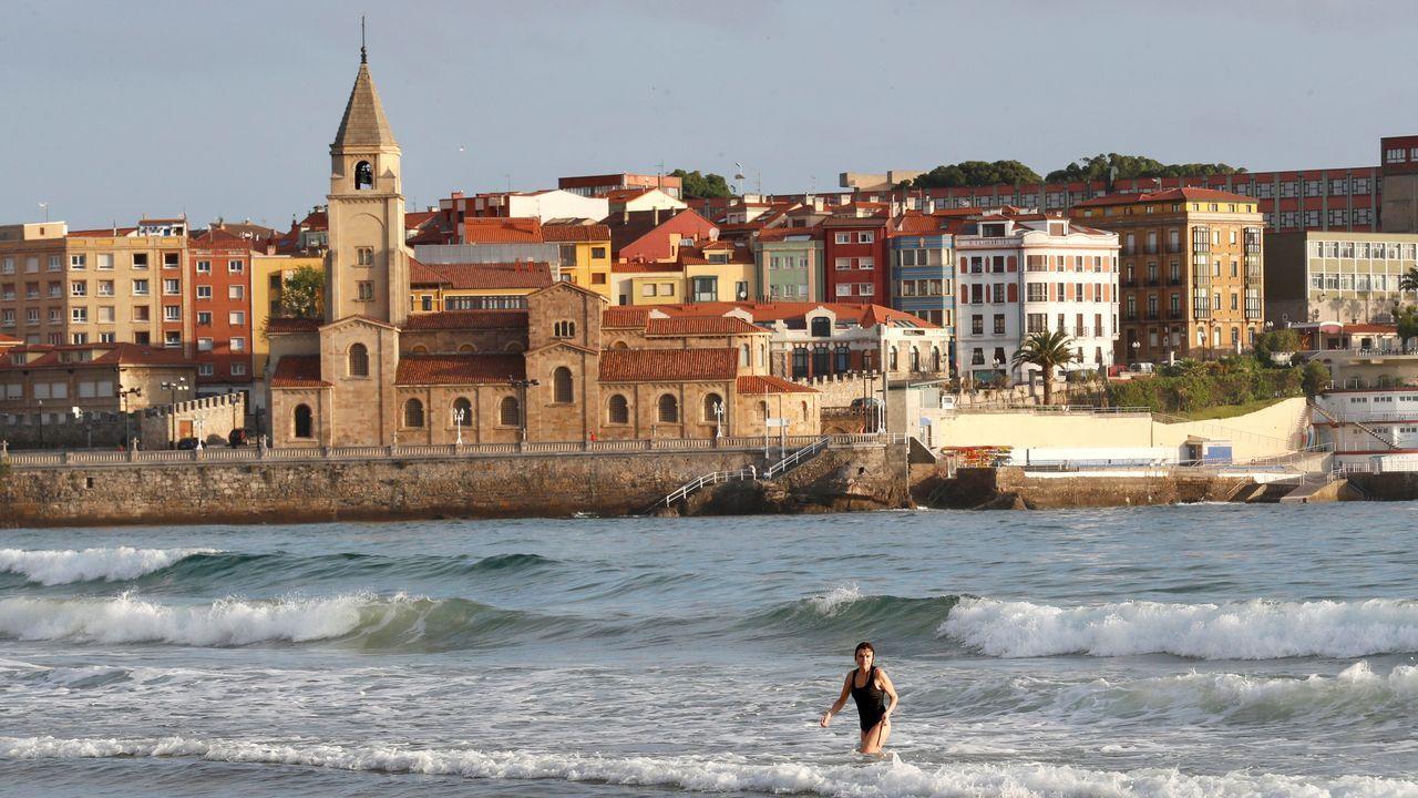 Bronco enfrentamiento en el Congreso entre el Gobierno y la oposición.Una mujer se baña en la mañana de hoy lunes en la playa de San Lorenzo de Gijón.
