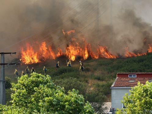 Helicóptero sobrevolando la zona afectada por el fuego en Rañobre, Arteixo