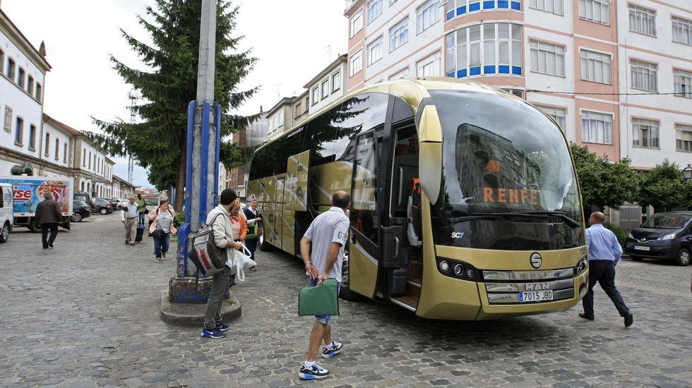 Viajeros de Renfe se suben a un autobús frente a la estación de Monforte para seguir viaje por carretera, en una foto de archivo