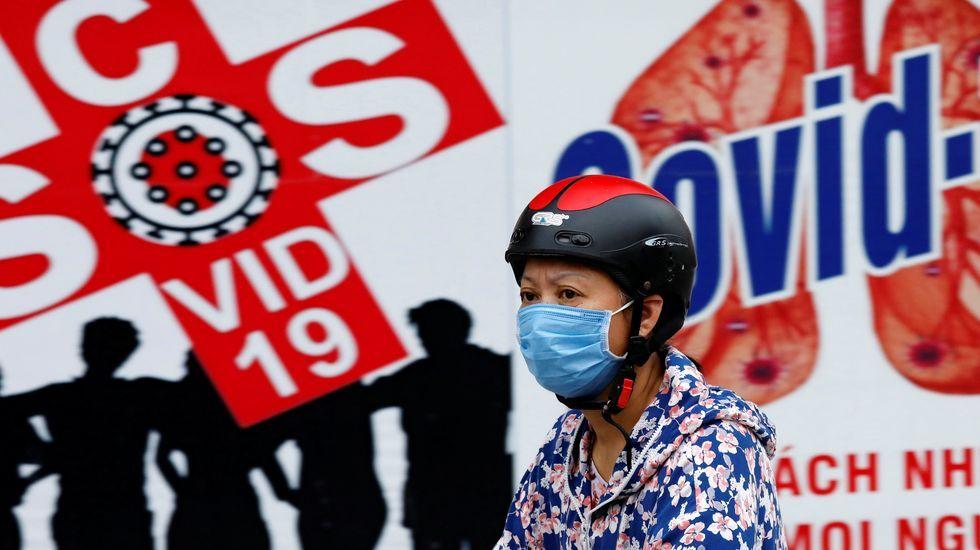 Una mujer vietnamita camina delante de un cartel informativo del covid-19