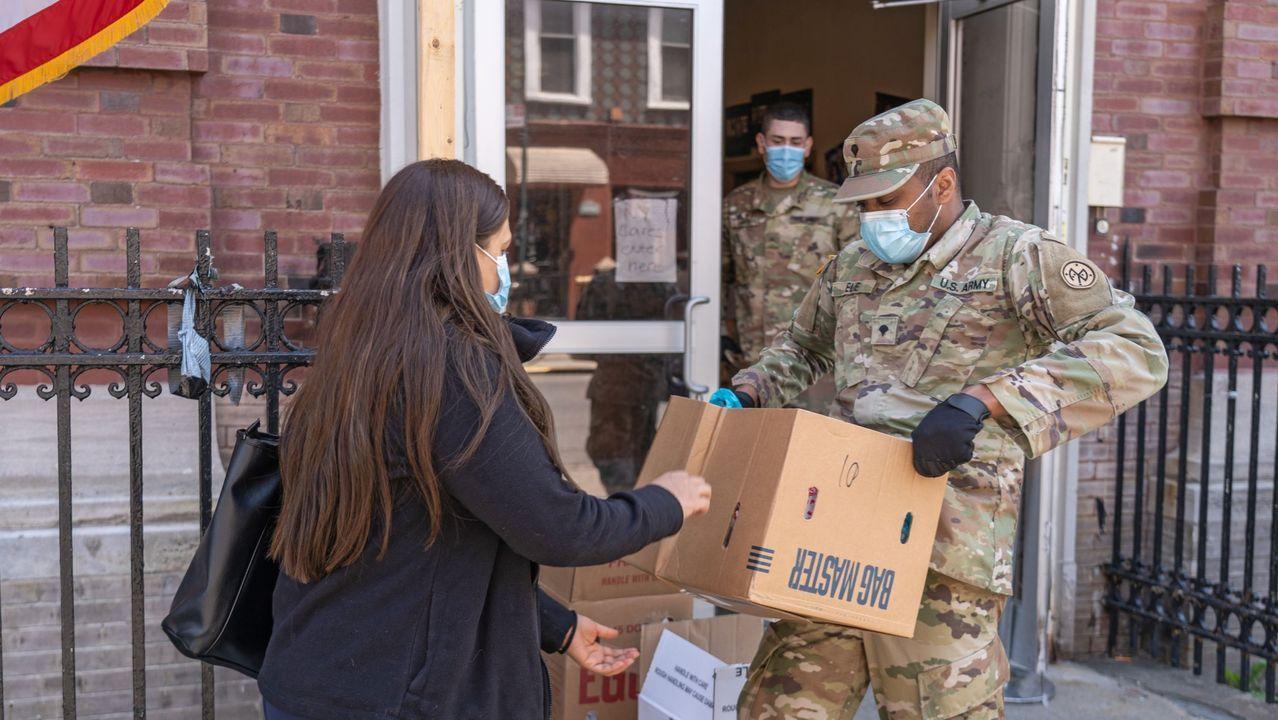 Miembros de la Guardia Nacional entregan cajas con comida y elementos esenciales, en medio de la pandemia del coronavirus, en New York, EEUU