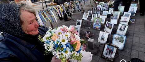 Una mujer llora al pide de las fotos que recuerdan o los más de cien manifestantes muertos en los enfrentamientos en Maidán.