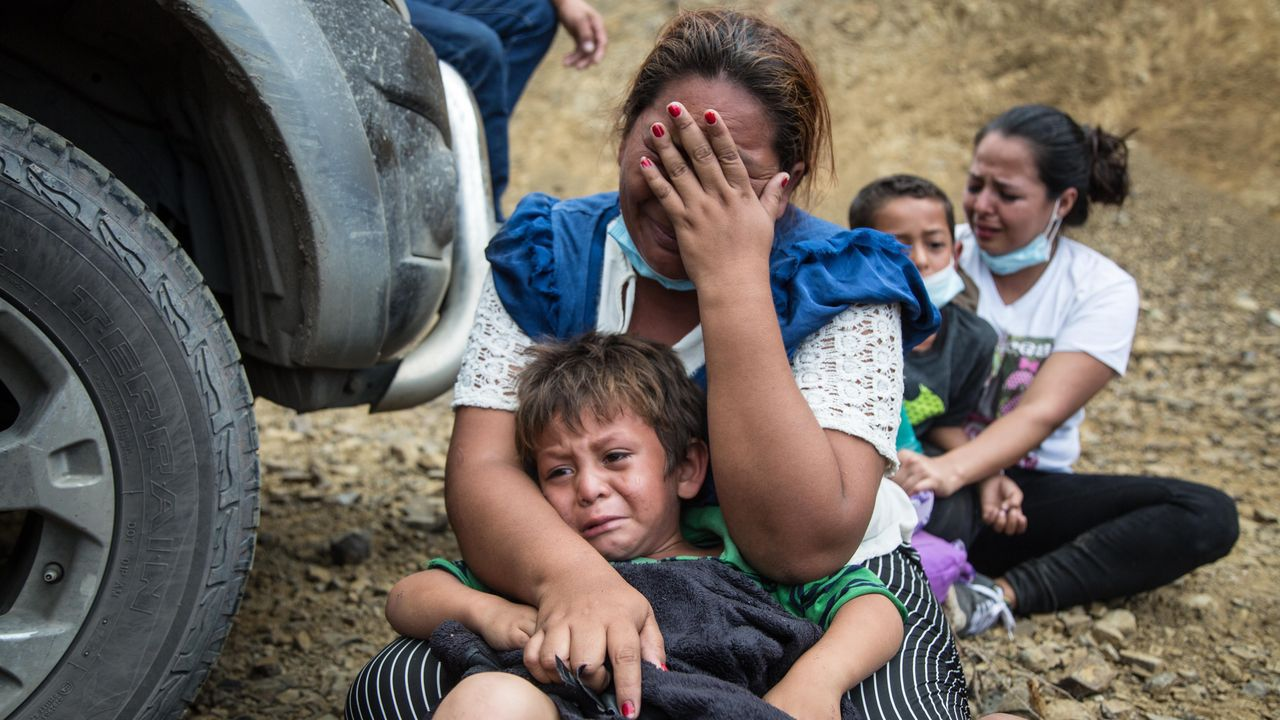 Una mujer y su hijo lloran sentados en el suelo después de que las fuerzas de seguridad de Guatemala disolviesen por la fuerza la caravana de migrantes procedentes de Honduras de la que forman parte