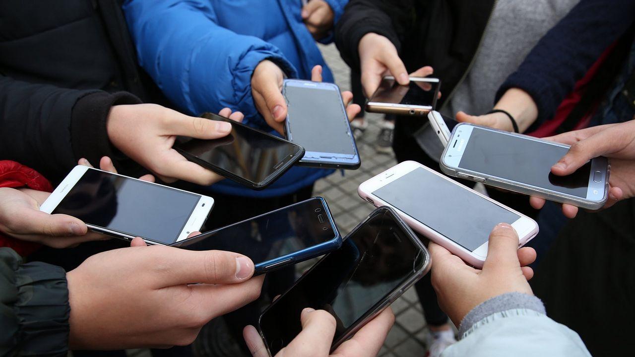 UN GRUPO DE ADOLESCENTES MOSTRANDO SUS TELEFONOS MÓVILES