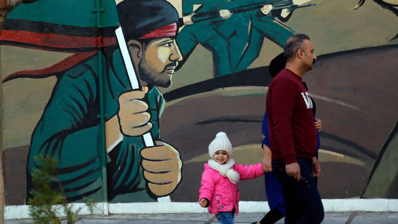 Una familia camina ante un mural en Teherán, la capital de la república islámica
