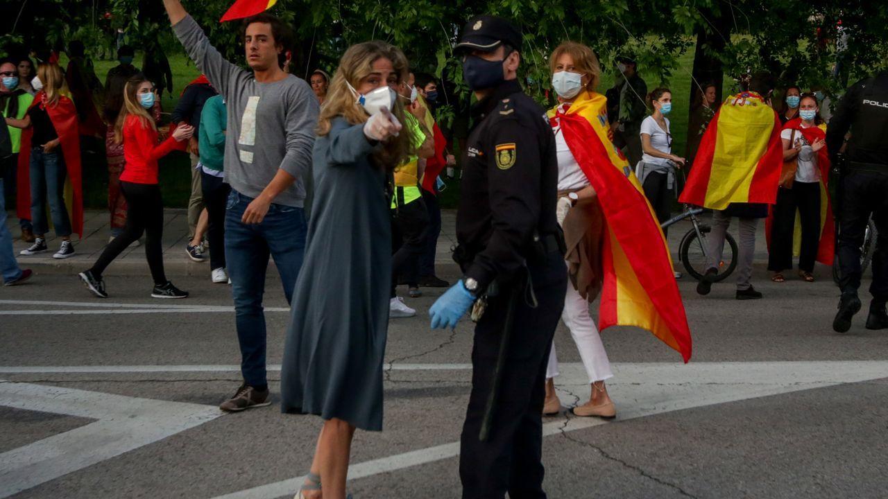 Cada vez son más las ciudades y barrios de Madrid que se suman a las caceroladas contra el Gobierno.Un agente conversa con una manifestante este lunes en el barrio de Salamanca