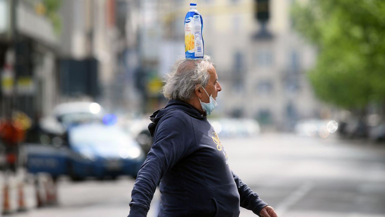 Un hombre con la mascarilla en el mentón y una botella en la cabeza cruza una calle en Milán, Italia