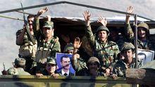 Soldados del Ejército sirio posan con una foto del presidente Bachar al Asad