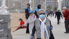 Personas mayores de 70 años pasean por el Muro de San Lorenzo, en Gijón