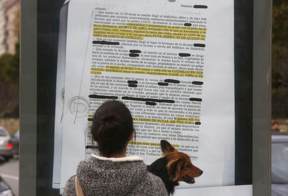 Una mujer lee una de las denuncias reales que se han llevado a vallas publicitarias de la ciudad.