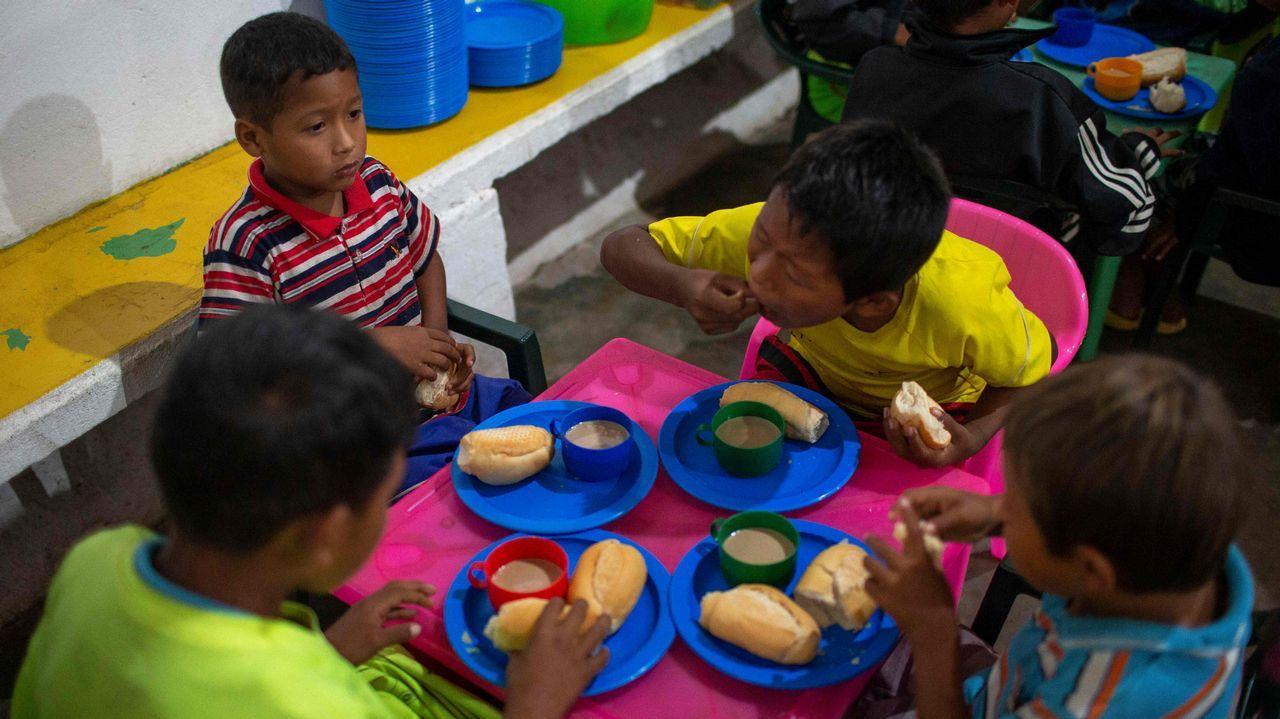 Niños venezolanos desayunan en la parroquia del sacerdote español José López Fernández de Bobadilla en Pacaraima, Roraima, Brasil