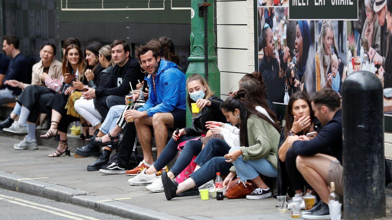 Jóvenes bebiendo en una calle de Londres, tras reabrir los locales comerciales