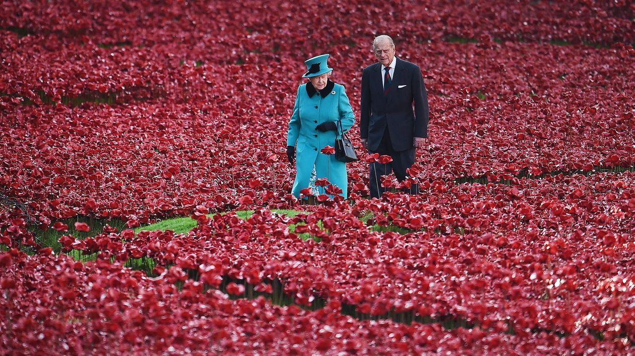 La reina Isabel II y el príncipe Felipe caminando entre amapolas rojas plantadas en el foso de la Torre de Londres en memoria de los británicos y de la Commonwealth muertos en la Primera Guerra Mundial