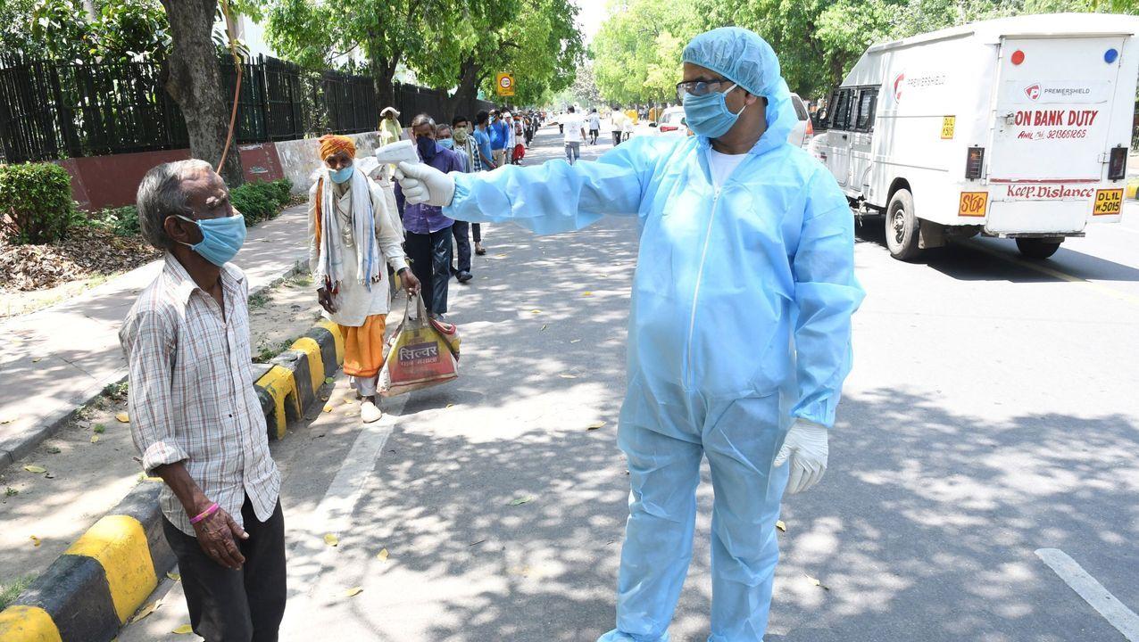 Un profesional sanitario realiza controles de temperatura en las calles de Nueva Delhi