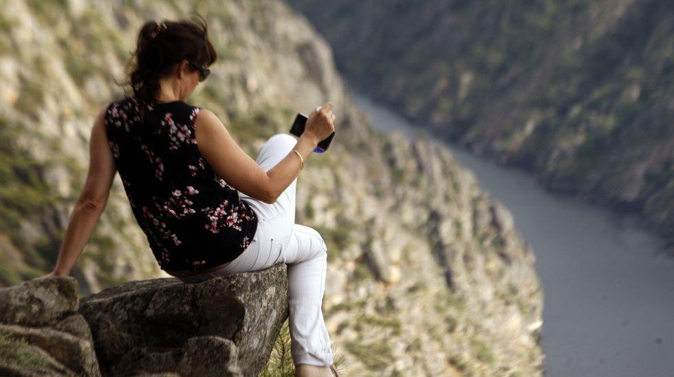Una mujer saca una foto del cañón del Sil en las cercanías del mirador de Santiorxo, en Sober