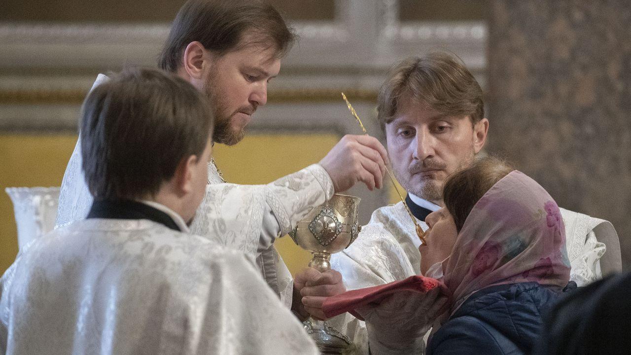 Los fieles reciben la comunión a través de una cuchara en una iglesia de San Petersburgo, a pesar de que se han establecido normas para garantizar la higiene