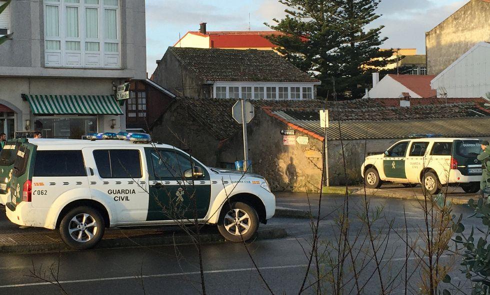 Vehículos patrulla de la Guardia Civil en las inmediaciones del piso de Muxía que fue registrado.