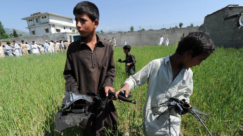 Fotografía tomada el 3 de mayo del 2011. Un grupo de niños recoge parte de las piezas del helicóptero estadounidense que participó en la operación que acabó con la vida del autor intelectual del 11-S.
