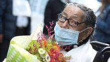 Una mujer de 92 años recibe flores tras curarse del covid en Colombia
