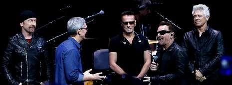 Los miembros del grupo U2, en el escenario con Tim Cook (de camisa azul), director ejecutivo de Apple.