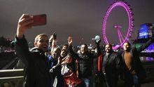Transeúntes se toman fotografías en el puente de Wensminster (Londres) para celebrar el cambio de año