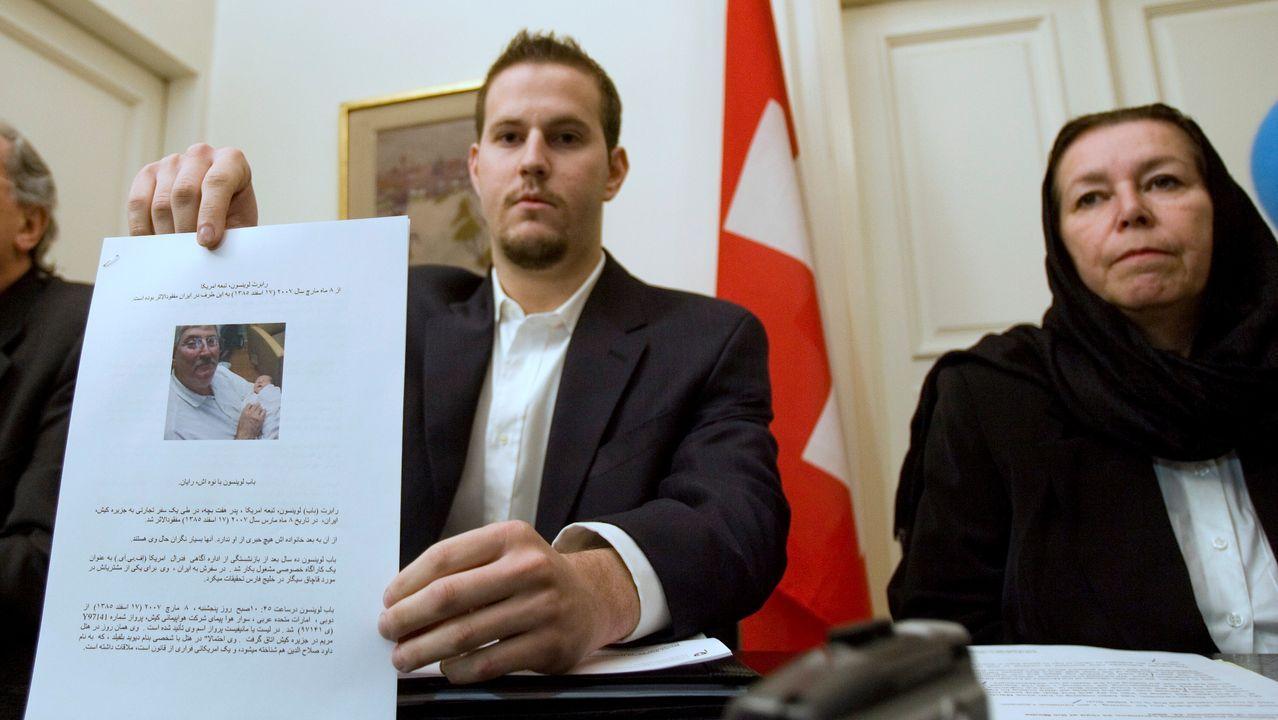 Christine Levinson observa cómo su hijo Daniel muestra la foto de su padre a los periodistas en la embajada de Suiza en Teherán el 22 de diciembre del 2007