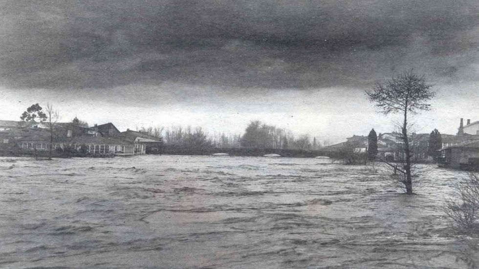 Imagen de la riada histórica del año 1909, el Cabe desbordado en el puente viejo