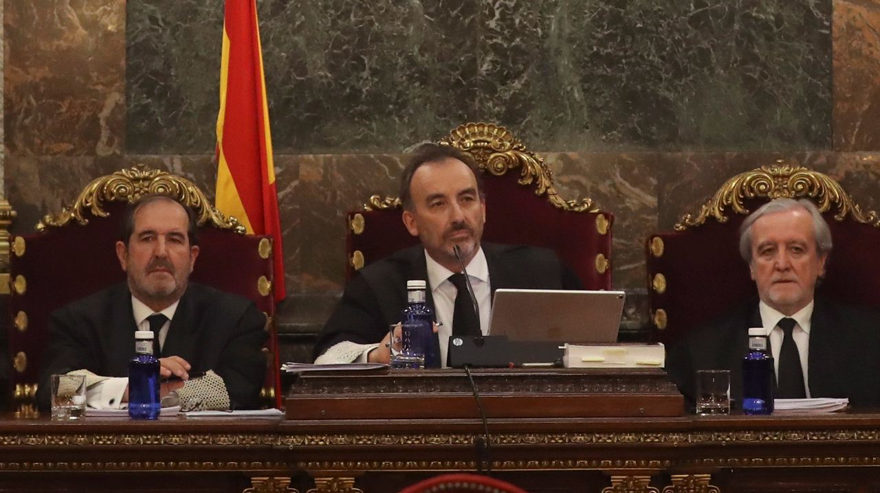 Seis de los 18 acusados por la DUI serán juzgados en Cataluña.El presidente del tribunal, Manuel Marchena, entre Andrés Martínez Arreieta y Juan Ramón Berdugo, al inicio de la vista