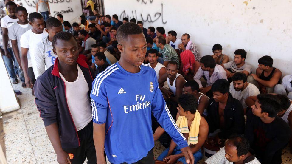 Inmigrantes rescatados por la guarda costera de Libia despues de que su barco se hundiese esperan en un centro de refugiados cercano a Tripoli