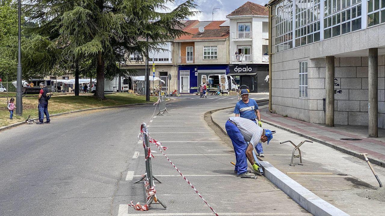 Abren, con cita previa, las oficinas del paro.Una mujer coloca un aviso en la persiana cerrada de un negocio del centro de Oviedo