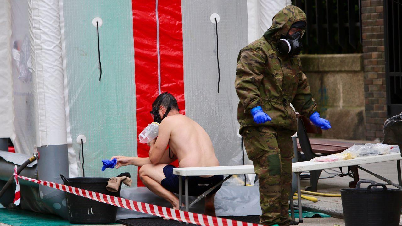 Un soldado se coloca los guantes de protección antes de pasar a la ducha descontaminante