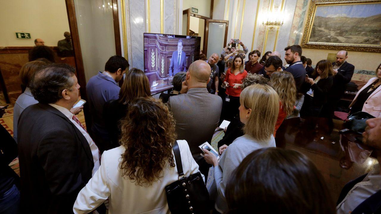 Varios periodistas siguen a través de una pantalla la intervención de Rajoy.