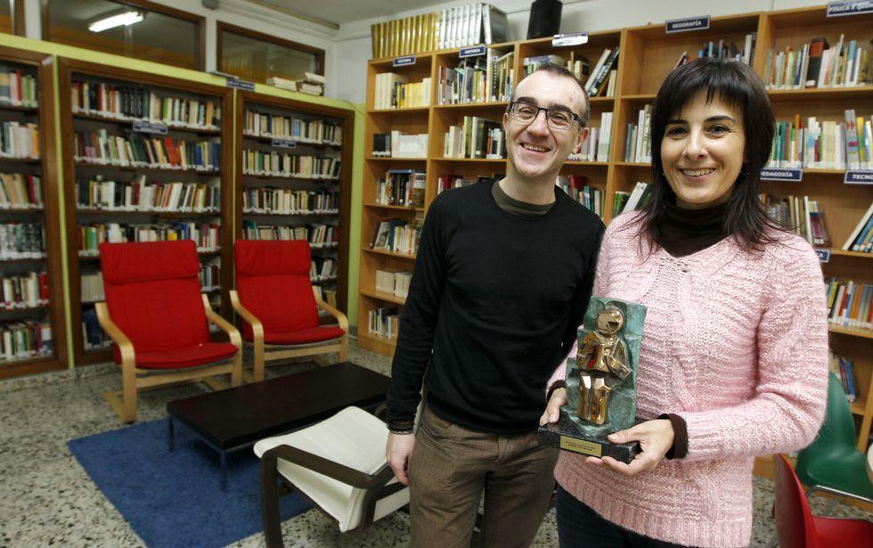 El director, Carlos Cid, y la responsable de la biblioteca, Guadalupe Vilar, con el premio que conceden las librerías de Galicia.