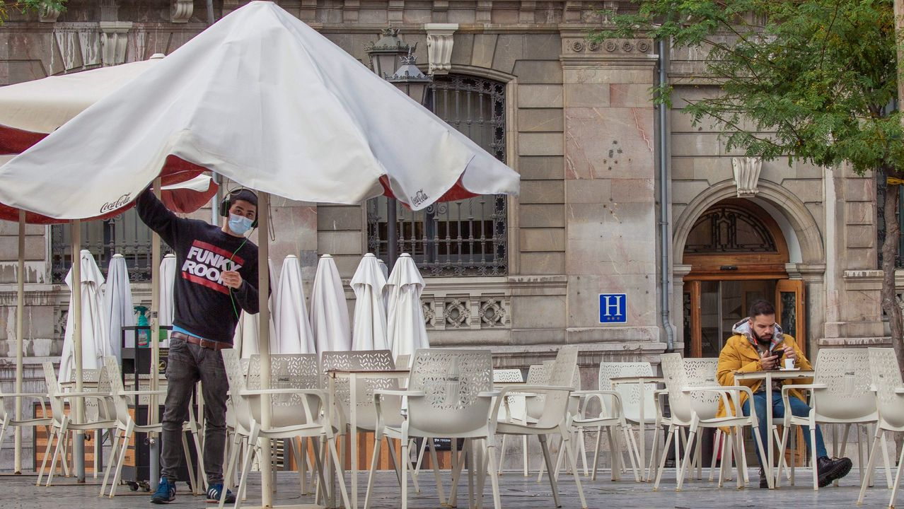 alumnos, estudiantes, universitarios.Un hombre toma un café en una terraza del centro de Oviedo