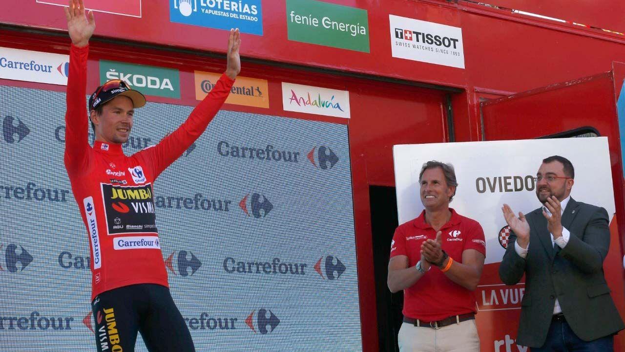 De derecha a izquierda, el presidente del Principado de Asturias, Adrián Barbón, junto a  César López, representante de la empresa Carrefour,  tras entregar al esloveno  Primoz Roglic el jersey rojo que le acredita como líder de la Vuelta