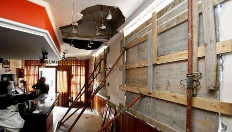 La operación policial en Santiago.Ayer comenzaron las obras de reparación de los daños en los edificios afectados por la explosión, como en esta cafetería.