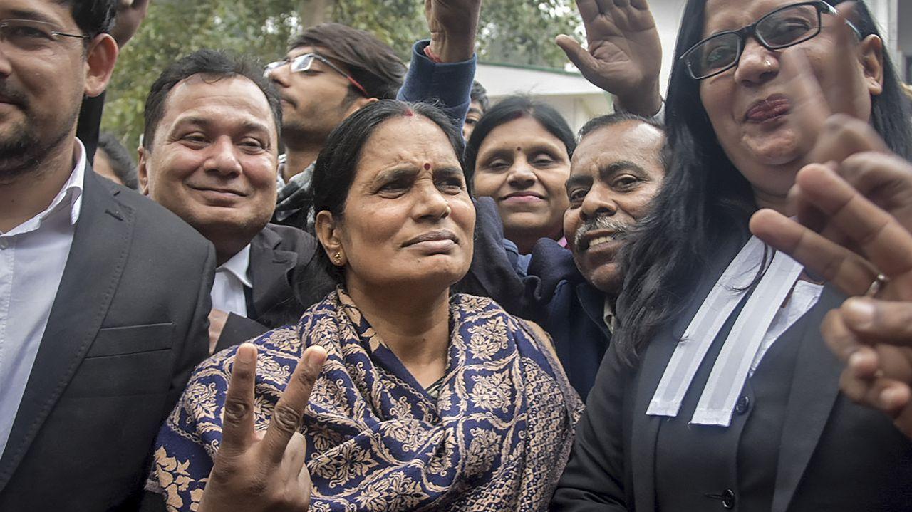 Amor, oración y homenajesa golpe de mascarilla.Asha Devi, la madre de la joven fallecida, abandonó el lugar de la ejecución haciendo el signo de la victoria