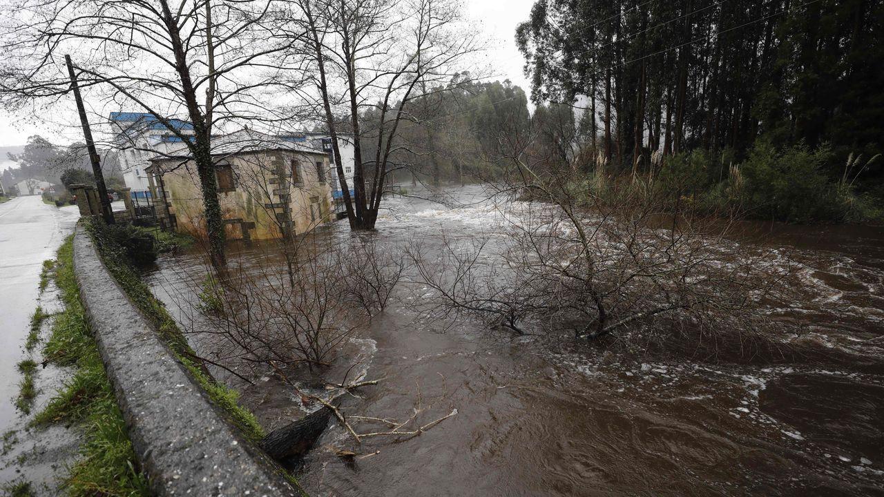 El cauce del río Landro en Viveiro crece por las fuertes lluvias y en el momento de la pleamar.Una antena cayó sobre la luna de un coche en la Rúa Magnolia
